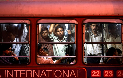 Commuters travel on a crowded bus in Mumbai